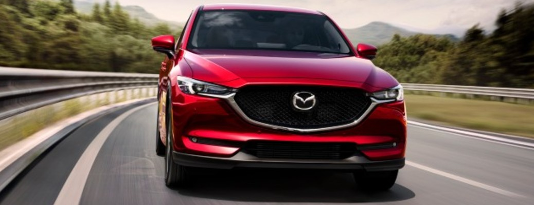 A red-colored 2021 Mazda CX-5 driving on a road