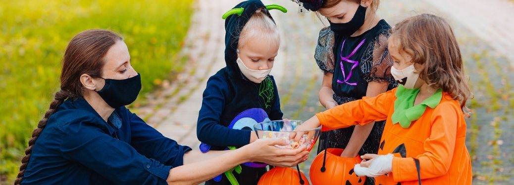 A woman distributing trick or treat candies to kids in Halloween costumes