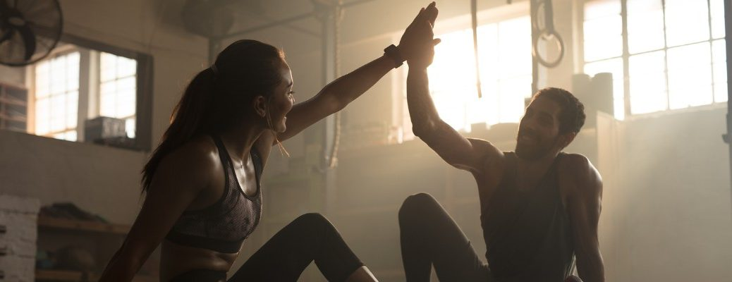 Man and woman high-fiving after workout