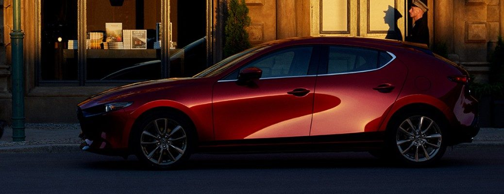 Profile view of red 2019 Mazda3 Hatchback parked in front of door