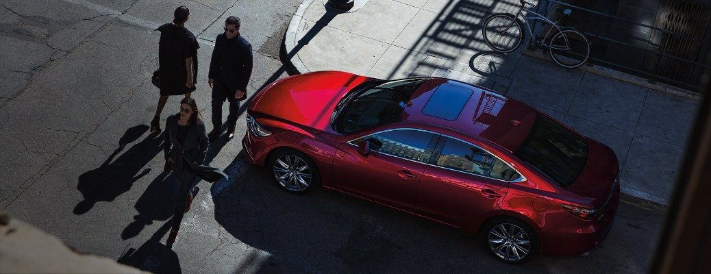 Two people walking in front of 2020 Mazda6