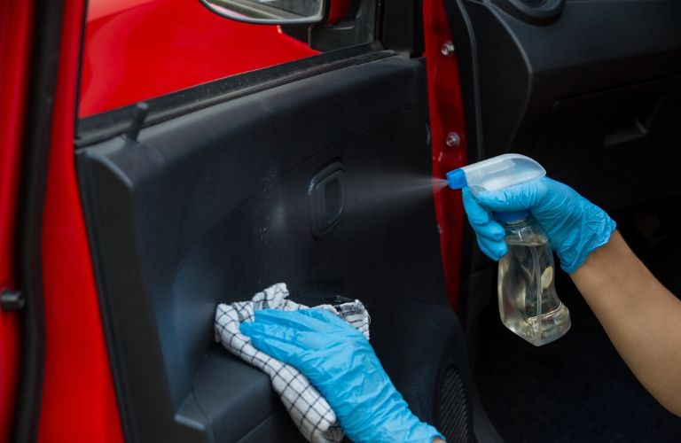Image of a person sanitizing the interior of their vehicle's door