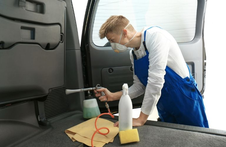 Image of a person sanitizing the interior of their vehicle