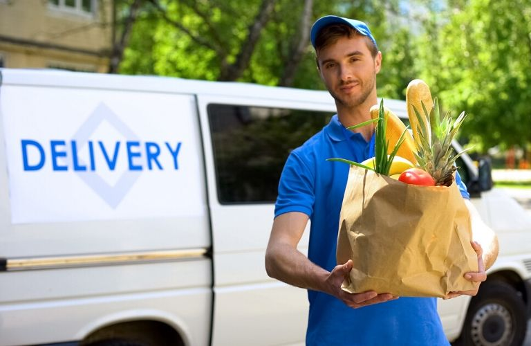 Image of a grocery delivery man bring groceries out of his truck