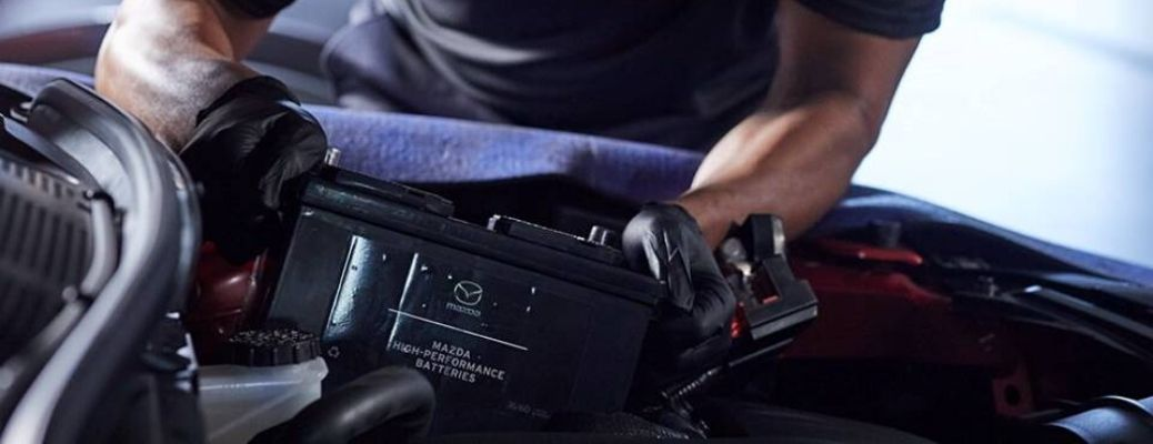 Image of a service technician replacing a Mazda battery