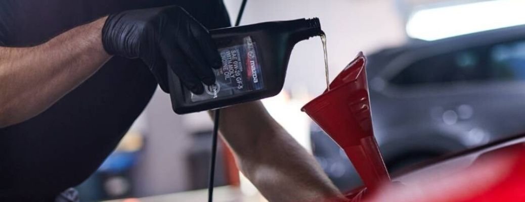 Image of Mazda oil being poured into a vehicle's engine