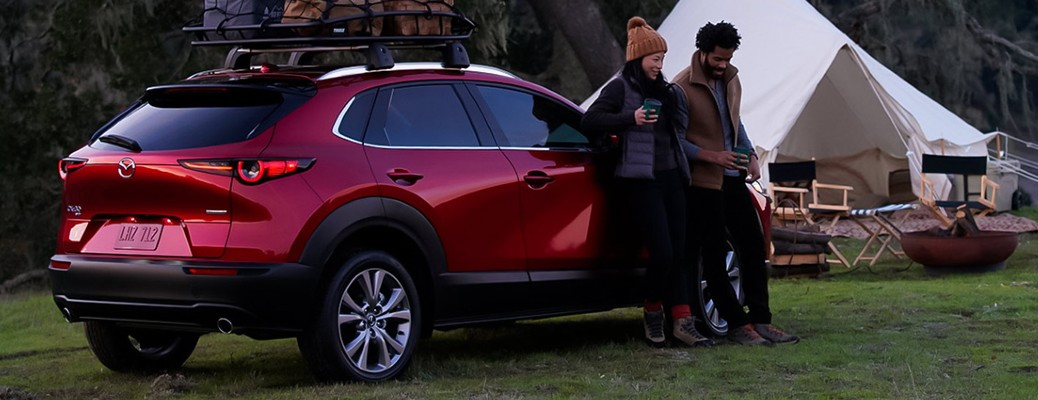 Red colored 2021 Mazda CX-30 parked near a man, woman, and white tent