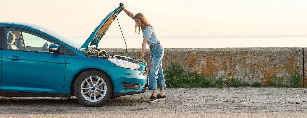 A woman looking under the hood of a blue-colored car while on the side of a street with a field in the background