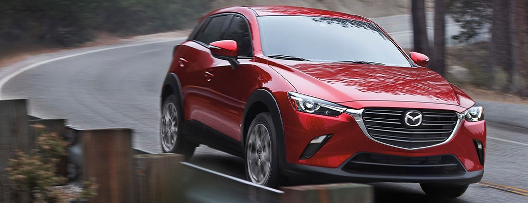 A red-colored 2021 Mazda CX-3 driving on a curved road