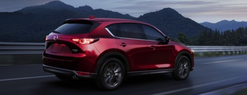 The 2021 MAzda CX-5 driving on a road when it is dark outside
