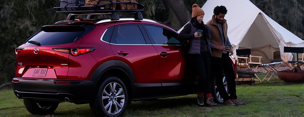Two people leaning against a 2021 Mazda CX-30 with a white tent in the background