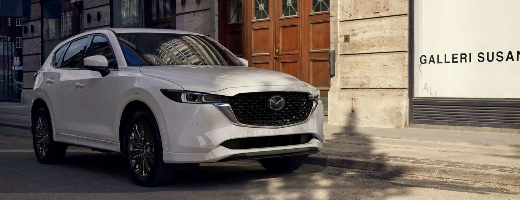 A white colored 2022 Mazda Cx-5 parked outside a gallery with a wooden door