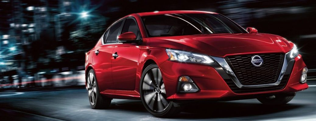 Front view of red 2019 Nissan Altima driving on dark city street