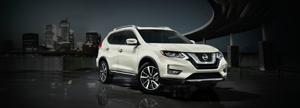 White 2020 Nissan Rogue with a city skyline in the background