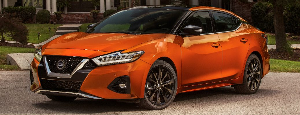 Orange 2020 Nissan Maxima parked in front of a brick house