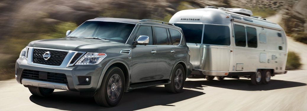 Grey 2020 Nissan Armada towing an Airstream trailer on a hilly road