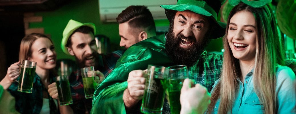 People drinking green beer and wearing green clothing at a St. Patrick's Day party