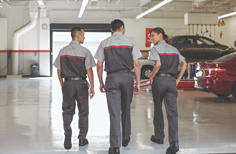 Image of three Toyota Service Technicians walking through their service center