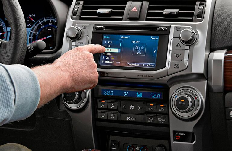 A man pressing a button on the 2019 Toyota 4Runner's touchscreen