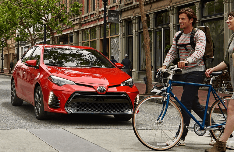 A man and woman walking bikes past the 2018 Toyota Corolla