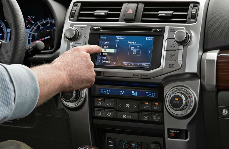 A hand touching the screen of the 2018 Toyota 4Runner infotainment system