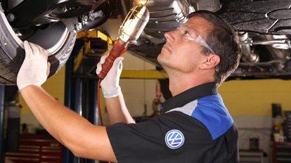 Volkswagen mechanic looking under car