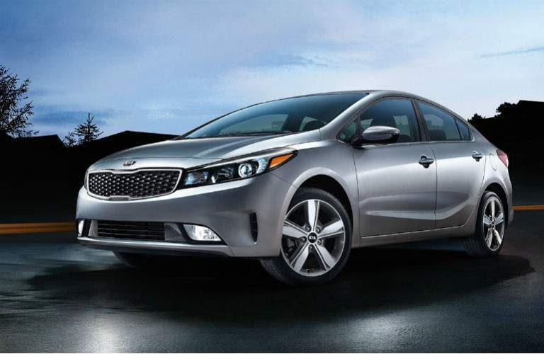 2018 kia forte silver in a graveyard at dark front three quarter view with drivers side focused