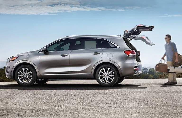 man approaching silver 2018 kia sorento on beach with luggage and power liftgate opening