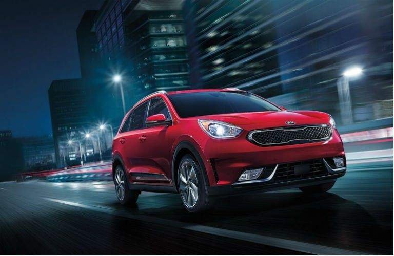 Red kia niro driving through city at night with streetlights on and no other cars