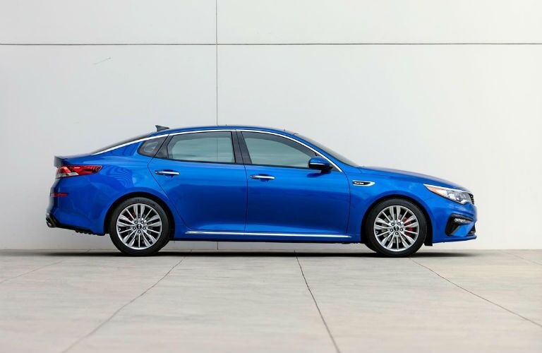 Blue 2019 Kia Optima parked by a white wall