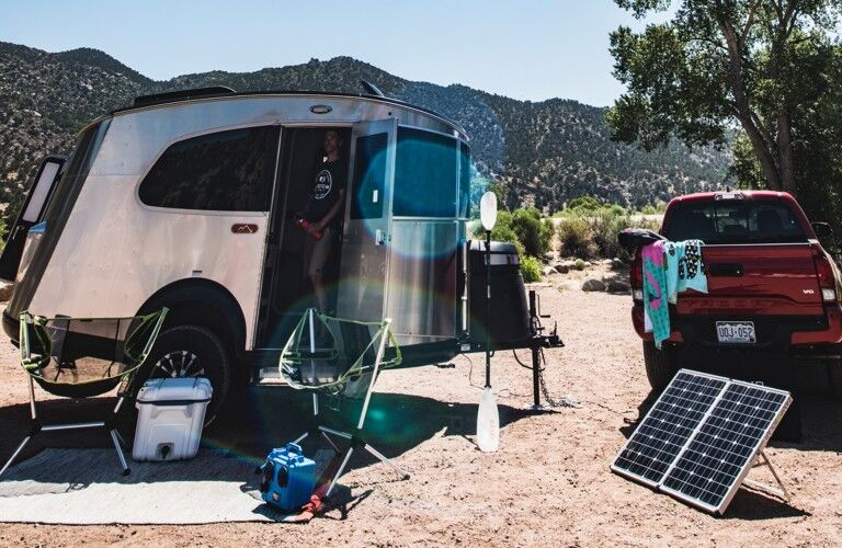 An exterior view of a 2020 Airstream Basecamp with a man looking outside of the model.