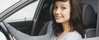 Woman looking through the driver's side door smiling