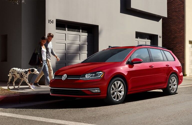 Front driver angle of a red 2019 Volkswagen Golf SportWagen parked on the side of a street with a couple and their dalmatian walking towards it
