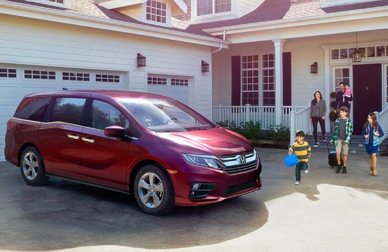 Front passenger angle of a red 2020 Honda Odyssey parked in front of a home with a family walking towards it