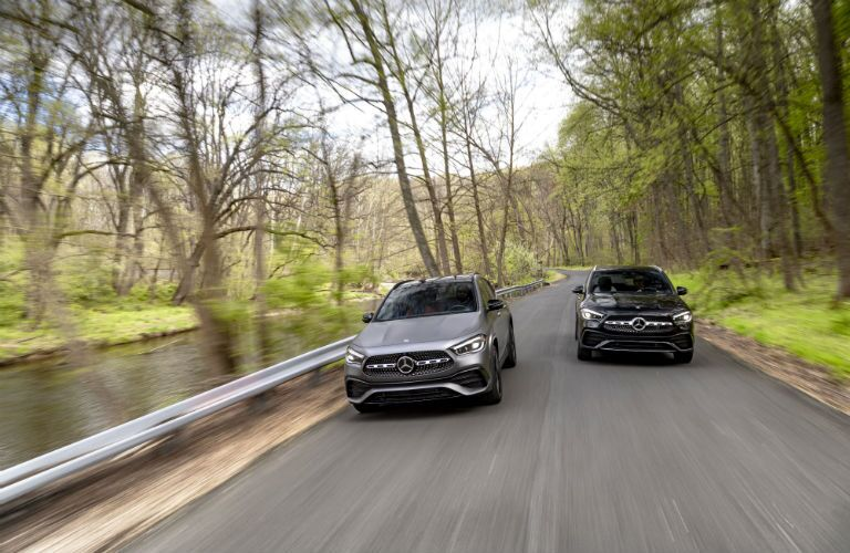 2021 MB GLA exterior front fascia of 2 models on wooded road