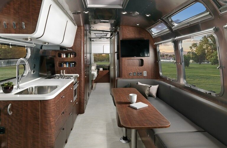 The interior view of the dinette and kitchen area inside a 2021 Airstream Globetrotter® 30RB.