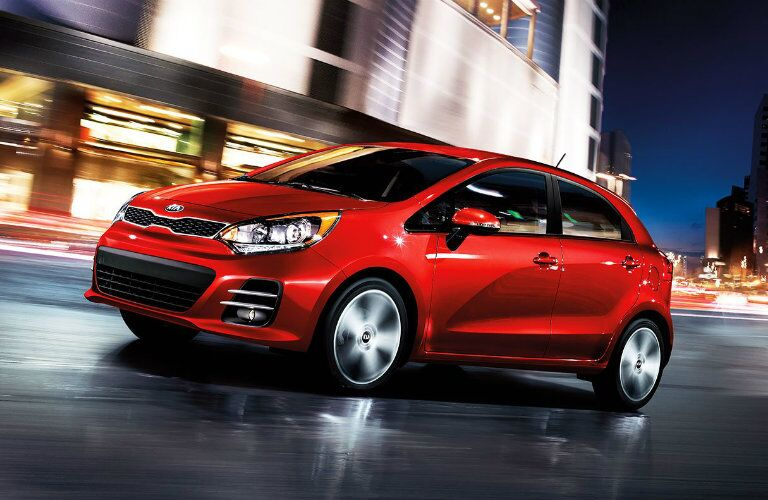 Front driver angle of a red 2016 Kia Rio driving down a road