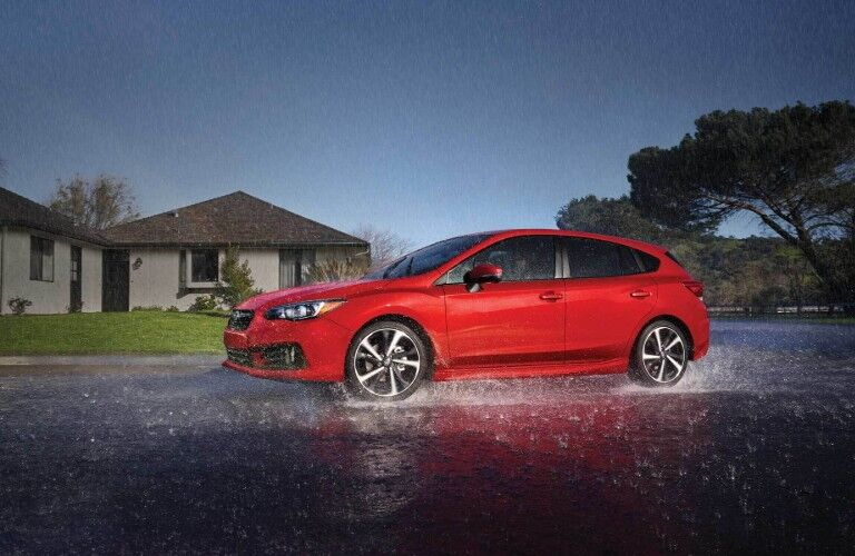 Front driver angle of a red 2020 Subaru Impreza driving on a wet road