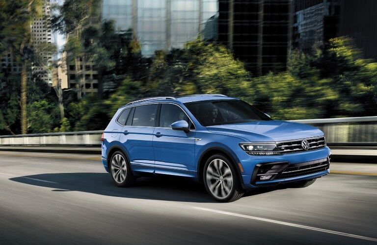 Front passenger angle of a blue 2020 Volkswagen Tiguan driving on a road