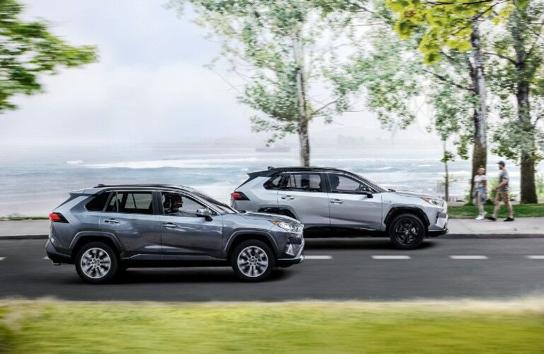 Two 2021 Toyota RAV4 models driving near water