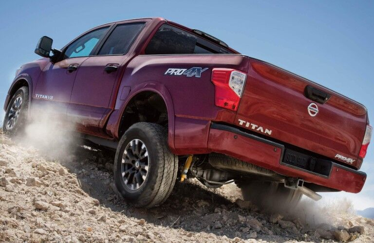 Rear driver angle of a red 2019 Nissan TITAN driving up a rocky slope