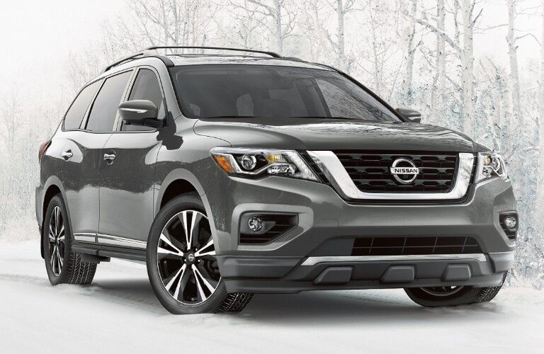 Front passenger angle of a grey 2020 Nissan pathfinder parked outdoors in the snow