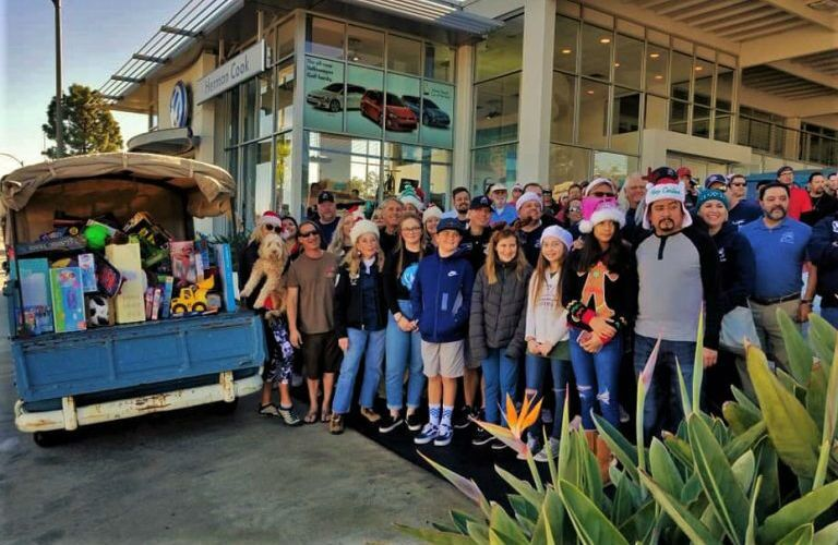 Herman Cook Volkswagen staff next to Toys for Tots donations