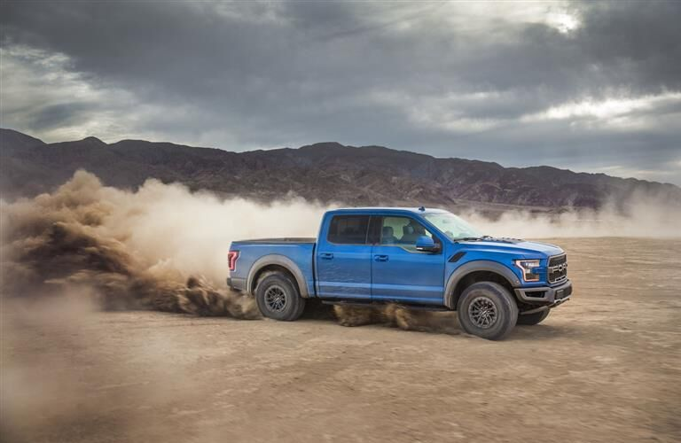 Dust flying from behind blue 2019 Ford F-150 Raptor