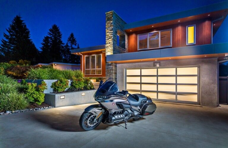 The front and side view of a gray 2018 Honda Gold Wing parked in front of a modern house.
