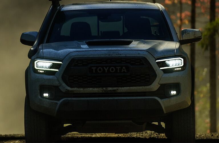A head-on photo of the 2020 Toyota Tacoma driving through the woods.