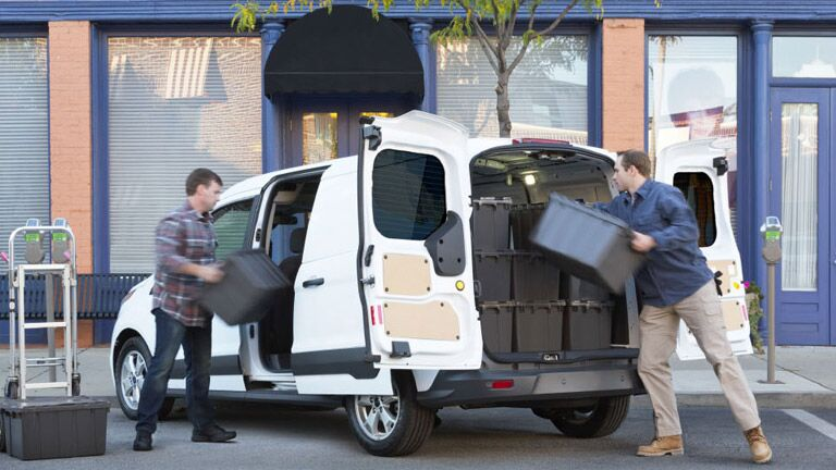 Tradesman charging cargo on the back of white 2015 Ford Transit Connect