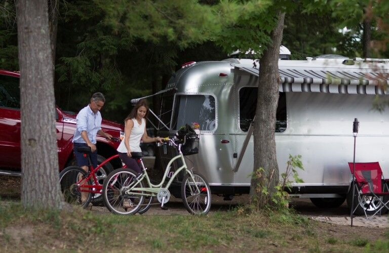 The front view of a 2021 Airstream Classic parked behind a couple with bicycles.
