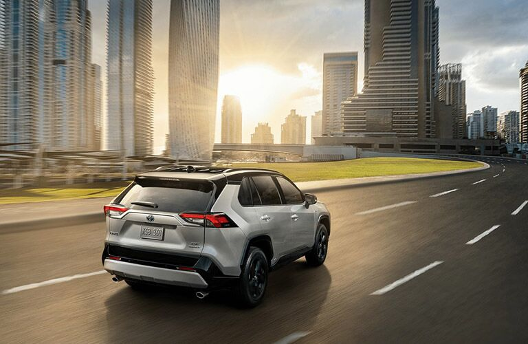 Grey 2020 Toyota RAV4 driving by tall buildings
