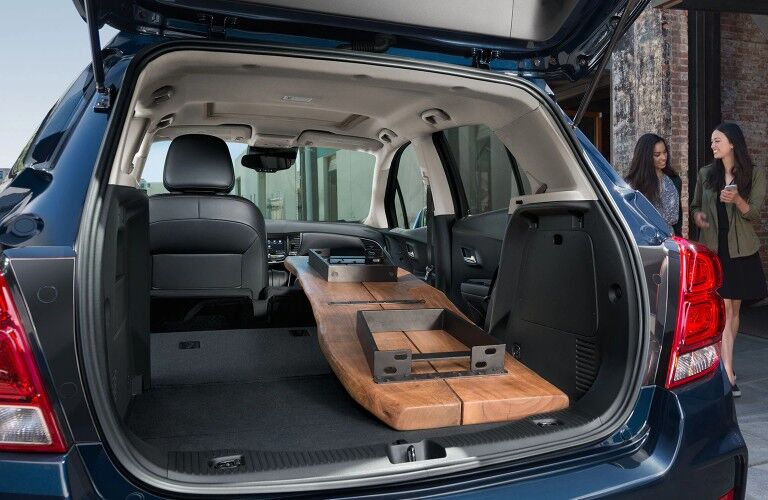 Rear angle of a the seats put down inside a blue 2020 Chevrolet Trax with a long board inside